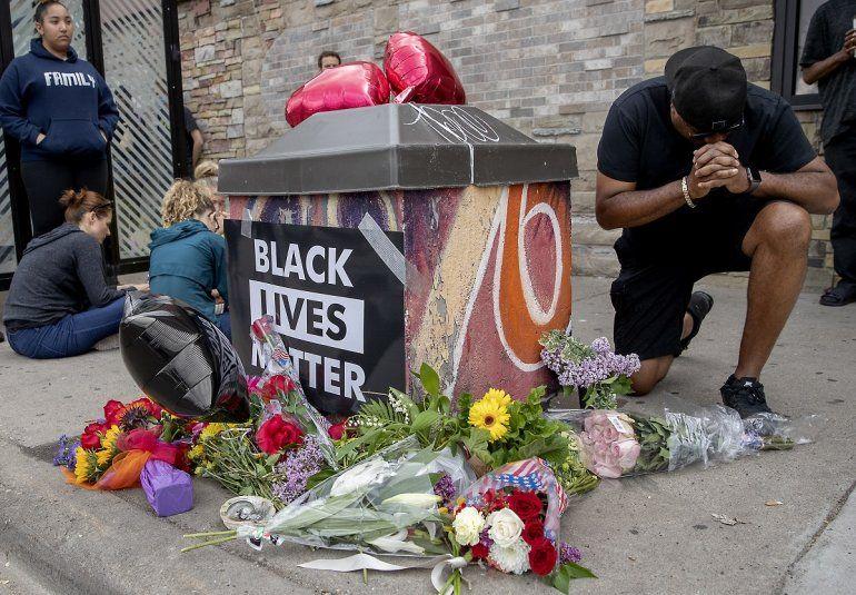 Varias personas se reúnen alrededor de un memorial improvisadopara honrar a George Floyd