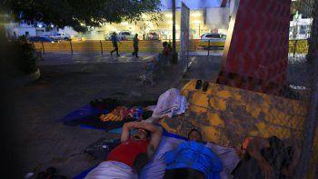 Migrantes que esperan respuesta a su solicitud de asilo en EEUU duermen en el puente internacional Puerta de México, en el estado mexicano de Tamaulipas.