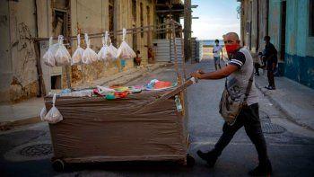 Un vendedor ambulante con una máscara como medida de precaución contra la propagación del nuevo coronavirus empuja su carro por una calle en La Habana, Cuba, el lunes 31 de agosto de 2020.