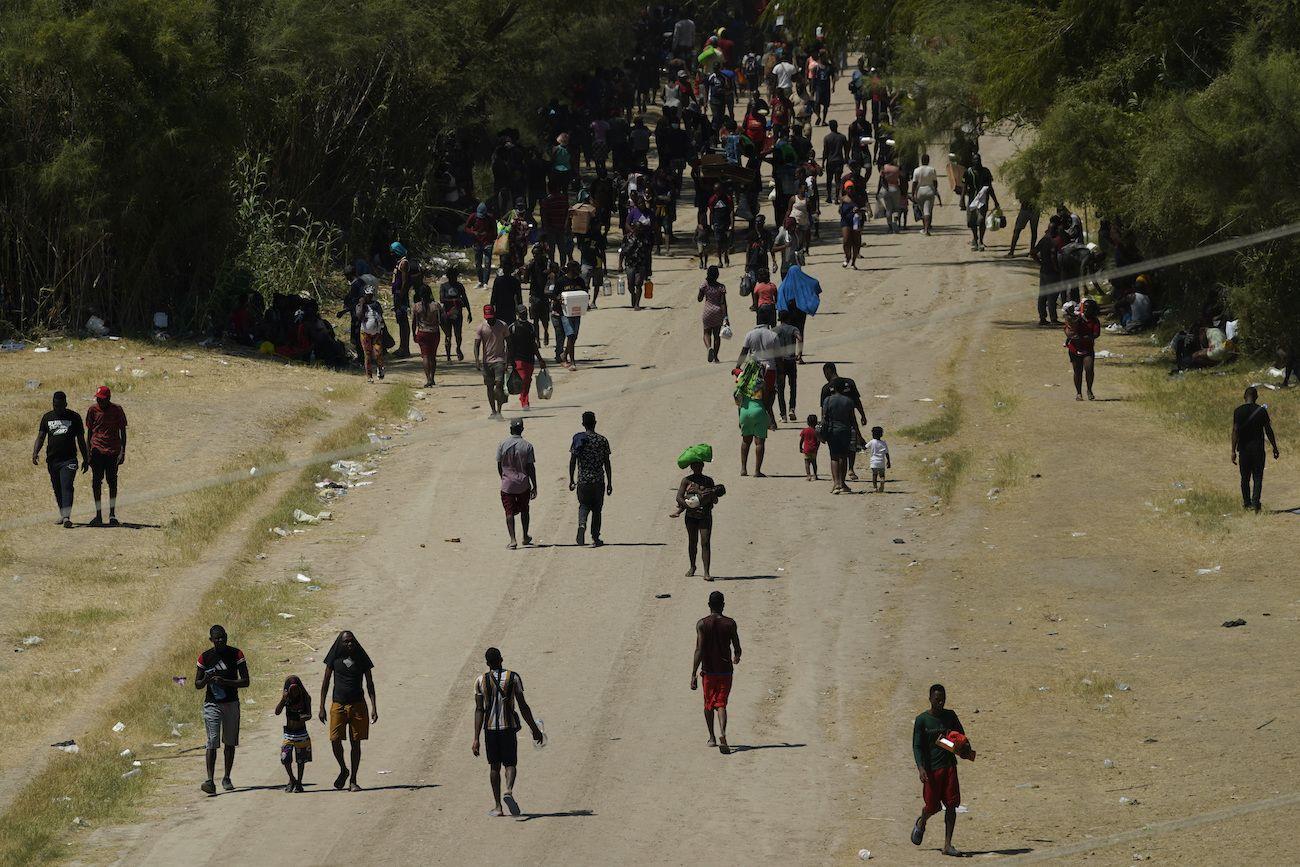 Migrantes haitianos caminan por un camino de tierra después de ingresar a Estados Unidos desde México, el viernes 17 de septiembre de 2021, en Del Rio, Texas.