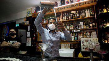 Con máscaras para protegerse del nuevo coronavirus, el bartender Dagoberto Jesús Morejón prepara un cóctel con plantas endémicas de Cuba, mientras su socio Manuel Alejandro Valdés lo respalda en La Habana, Cuba, el martes 13 de octubre de 2020.