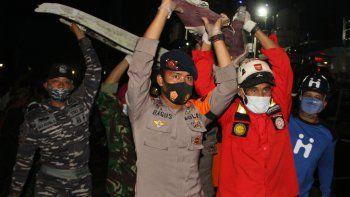 El personal de rescate de Indonesia transporta piezas de los restos recuperados del lugar del accidente del vuelo SJ182 de Sriwijaya Air en el puerto de Yakarta el 10 de enero de 2021, luego del accidente del 9 de enero del avión Boeing 737-500 de la aerolínea en el mar de Java minutos después del despegue.