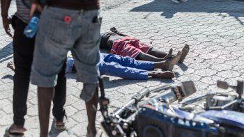 Los cuerpos de dos internos muertos yacen en la acera de la prisión de Croix-des-Bouquets de donde escaparon muchos presos y donde murieron varias personas, en Croix-des-Bouquets, suburbio de la capital haitiana, el 25 de febrero de 2021. Múltiples personas murieron el 25 de febrero en Haití, incluido el director de una prisión en los suburbios de la capital, Puerto Príncipe, luego de que varios presos escaparan, dijo la policía. El inspector de división Paul Hector Joseph, que está a cargo de la prisión civil de Croix des Bouquets, fue asesinado en la prisión, Gary Desrosiers, portavoz de la policía nacional de Haití
