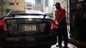 Un trabajador llena el tanque de un vehículo en una gasolinera de Caracas el 5 de octubre de 2020, en medio de la nueva pandemia de coronavirus. Venezuela lanzó este lunes un plan para distribuir gasolina según los números de matrícula de los vehículos, una medida en respuesta a la severa escasez de combustible en el país caribeño.