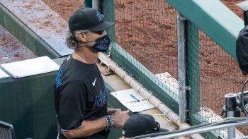 El manager de los Miami Marlins, Don Mattingly, se asoma desde el banquillo durante la octava entrada de un juego de béisbol contra los Filis de Filadelfia, el sábado 25 de julio de 2020 en Filadelfia.