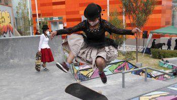 Ayde Choque, con una máscara en medio de la pandemia de COVID-19, salta con su patineta durante un show de talentos juveniles en La Paz, Bolivia, el miércoles 30 de septiembre de 2020. Un colectivo de mujeres jóvenes llamado ImillaSkate, una mezcla de aymara e inglés que significa niña y el deporte con patineta, usa la ropa tradicional indígena como una declaración de orgullo de su cultura indígena al andar en skate.