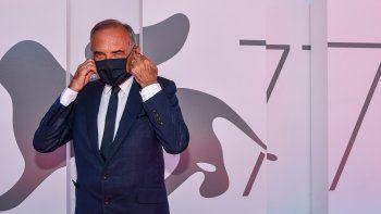 El director del Festival de Cine de Venecia, Alberto Barbera se pone una mascarilla mientras posa fuera del palacio del festival en la víspera de la inauguración del 77 Festival de Cine de Venecia, el 1 de septiembre de 2020 en el Lido de Venecia.