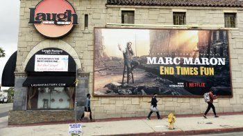 Los peatones pasan junto al club de comedia cerrado Laugh Factory, el lunes 16 de marzo de 2020, en Los Ángeles. El alcalde de Los Ángeles, Eric Garcetti, ordenó el domingo el cierre de todos los bares, clubes nocturnos, restaurantes, gimnasios y lugares de entretenimiento de la ciudad para evitar la propagación del coronavirus.