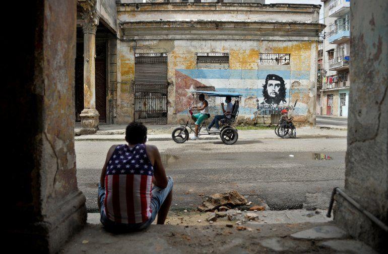 Un hombre vestido con una camiseta sin mangas con un diseño de la bandera de Estados Unidos descansa en La Habana el 21 de octubre de 2020