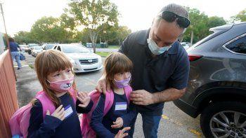 Anthony Sacco deja a sus hijas Angelina, de 7 años, (izquierda), y Victoria, de 5, para su primer día de clases en la primaria Fox Trail, el viernes 9 de octubre de 2020, en Davie, Florida.