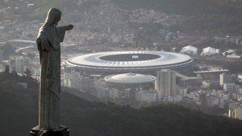 - En esta foto del 13 de mayo de 2014, vista del estadio Maracaná detrás del Cristo Redentor en Río de Janeiro. Brasil será la sede de la Copa América por segunda edición seguida.