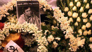 Una foto del fallecido actor indio Soumitra Chatterjee se ve en guirnaldas colocadas junto a su cuerpo durante su funeral en Calcuta el 15 de noviembre de 2020.