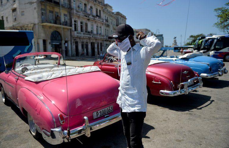 Un chofer de un auto privado al servicio del transporte del turismo se coloca una mascarilla ante el riesgo de contagio por coronavirus