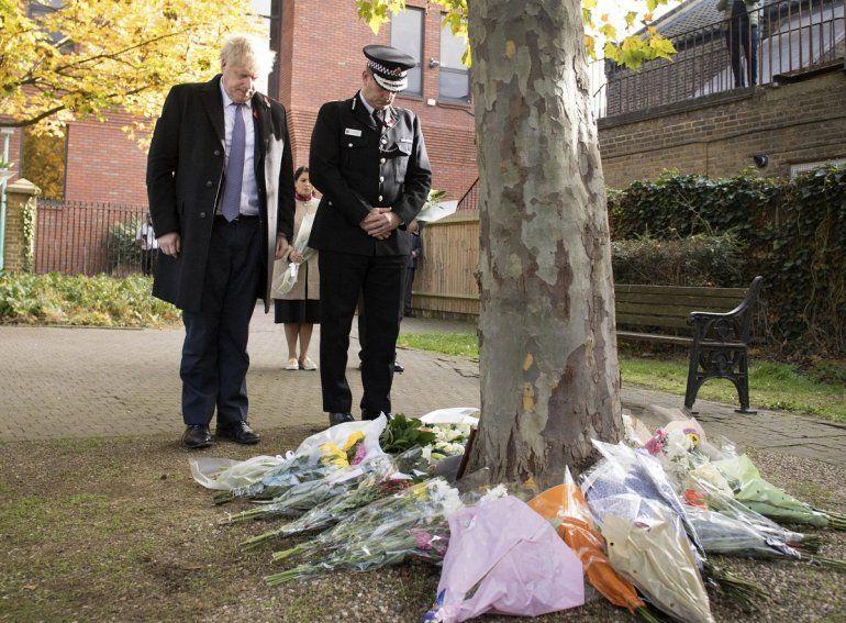 El primer ministro británico Boris Johnson está parado junto al jefe de la policía de Essex Ben-Julian Harrington después de depositar flores durante una visita a las oficinas del Concejo de Thurrock