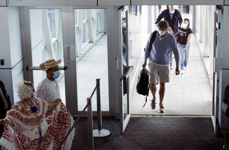 Pasajeros fueron recibidos este lunes 12 de ocubre por artistas con vestimentas tradicionales al llegar al Aeropuerto Internacional de Tocumen en la Ciudad de Panamá. (AP Foto/Arnulfo Franco)