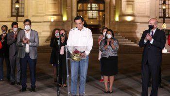 El presidente de Perú, Martín Vizcarra, baja la mirada mientras miembros de su gabinete lo aplauden frente al palacio presidencia en Lima, después de que el Congreso aprobó su destitución el lunes 9 de noviembre de 2020.