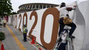 Obreros colocan logos en una barrera frente al Estadio Nacional, sede de la ceremonia de apertura y otras competencias de los aplazados Juegos Olímpicos de Tokio, el miércoles 2 de junio de 2021