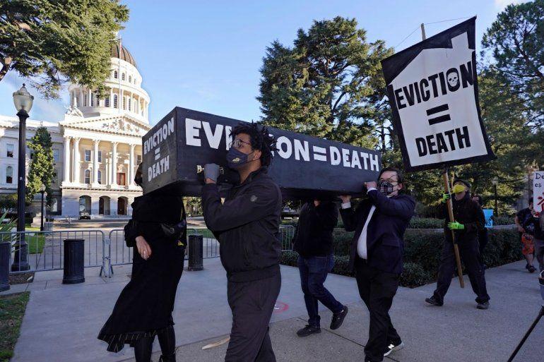 Manifestantes exigen la aprobación de una ley para condonar la renta e imponer protecciones más fuertes frente a los desahucios mientras cargan lo que parece un féretro frente al Capitolio de Sacramento