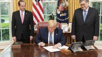 Donald Trump, presidente de los EEUU, firma una orden ejecutiva el 23 de marzo de 2020 en la Casa Blanca. Ala derecha, el fiscal general William Barr.
