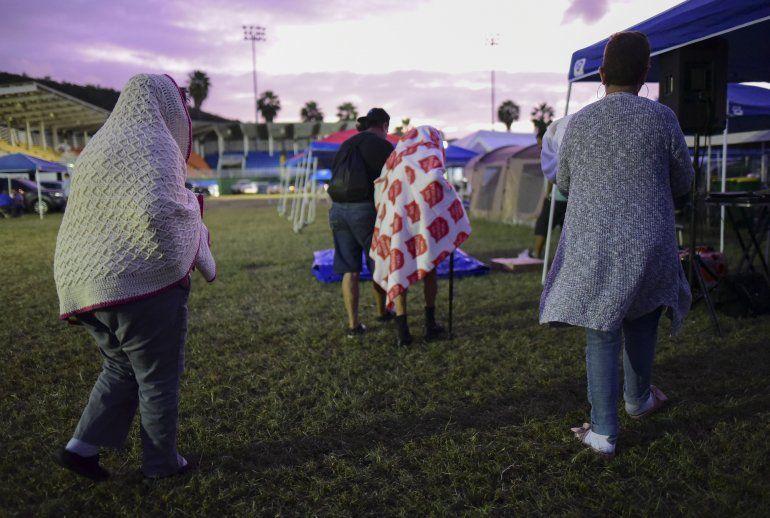 Varias personas se ponen de pie luego de pasar la noche en un estadio de béisbol tras un sismo de magnitud 6