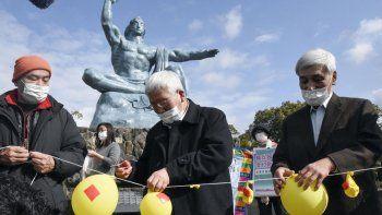 Asistentes desinflan globos simbolizando la esperanza de neutralizar y destruir la ojivas nucleares, durante un acto en el Parque de la Paz de Nagasaki, en el sur de Japón, el 22 de enero de 2021.