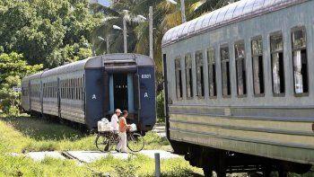 Fotografía de archivo fechada en agosto de 2018 de dos personas que caminan entre dos vagones de un tren de pasajeros en las inmediaciones de una estación de trenes en La Habana, Cuba.