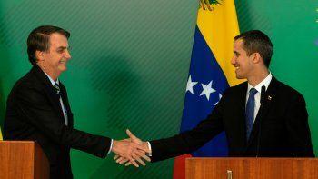 El presidente de Brasil, Jair Bolsonaro (izq.), saluda al jefe del Parlamento y presidente encargado de Venezuela, Juan Guaidó (der.) en el Palacio del Planalto, en la ciudad de Brasilia, el 28 de febrero de 2019.
