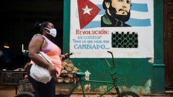 """Una mujer con mascarilla camina cerca de un cartel que representa al fallecido líder cubano Fidel Castro en el que se lee """"La revolución está cambiando todo lo que hay que cambiar"""" en La Habana, el 21 de enero de 2021."""