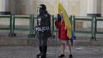 En esta imagen, tomada el 21 de septiembre de 2020, una mujer con una bandera colombiana, junto a un agente antimotines durante una protesta en Bogotá, Colombia. Sindicatos y grupos de estudiantes convocaron manifestaciones contra la brutalidad policial, la inseguridad y la crisis provocada por la pandemia del coronavirus.
