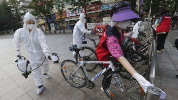 Trabajadores y voluntarios desinfectan bicicletas como medida de precaución contra el coronavirus en una calle en Goyang, Corea del Sur, el 25 de agosto de 2020.