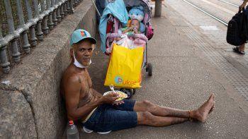 Un hombre mira a la cámara mientras come el almuerzo donado por la Fundación Leao XIII durante la pandemia de COVID-19, el miércoles 7 de abril de 2021, en Río de Janeiro