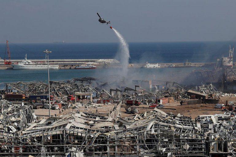 Un helicóptero del Ejército libanés arroja agua sobre el sitio de una explosión en el puerto de Beirut el miércoles
