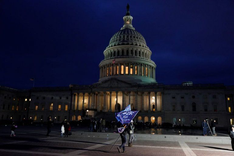 Un partidario del presidente Donald Trump sostiene una bandera en favor del mandatario afuera del Capitolio