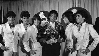 En esta foto del 28 de febrero de 1984, Michael Jackson, en el centro, posa entre bambalinas con el grupo Menudo durante la ceremonia de los premios Grammy en Los Ángeles. De izquierda a derecha Charlie Massó, Robby Rosa, Roy Roselló, Jackson, Ray Reyes y Ricky Meléndez. Reyes, miembro de Menudo durante la era dorada del quinteto puertorriqueño, murió el viernes 30 de abril de 2021. Tenía 51 años.