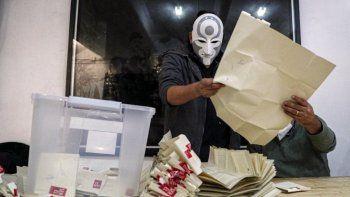 Un trabajador electoral con una máscara del personaje Amon, de la serie animada Leyenda de Korra, cuenta las papeletas después del segundo día de la elección de la Convención Constitucional para seleccionar a los miembros de la asamblea que redactarán una nueva constitución, en Santiago, Chile, el domingo 16 de mayo de 202.