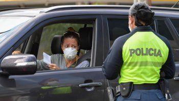 Una oficial de policía le pide a la conductora un permiso especial que le permite salir de su casa, en la ciudad de Panamá el 25 de marzo de 2020.Panamá se encuentra en cuarentena desde el 24 de marzo porcausa de la pandemia mundial del nuevo coronavirus, COVID-19.
