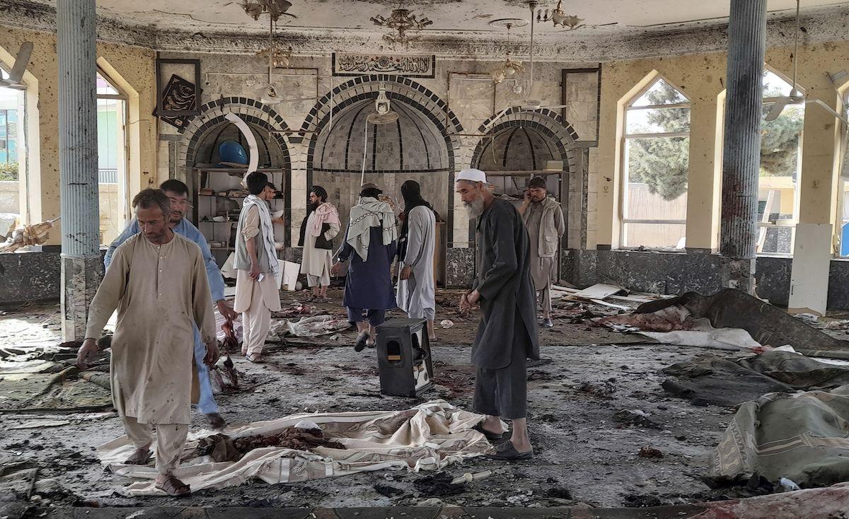 Varias personas inspeccionan los daños en el interior de una mezquita tras una explosión en Kunduz, Afganistán, el viernes 8 de octubre de 2021.