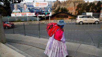 Una mujer camina cerca de un cartel del candidato presidencial Carlos Mesa, del partido Comunidad Ciudadana, en El Alto, Bolivia, un día antes de las elecciones presidenciales.