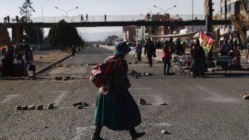 Una mujer que usa una mascarilla para prevenir el nuevo coronavirus camina por una calle bloqueada por manifestantes que protestan contra la postergación de las elecciones presidenciales en El Alto, Bolivia, el miércoles 5 de agosto de 2020.