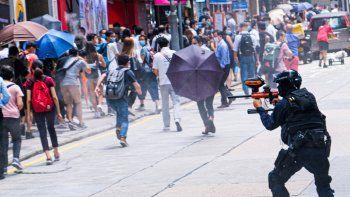China, Hong Kong: un agente de la policía antidisturbios dispara proyectiles de gas pimienta a los manifestantes durante una manifestación contra la segunda lectura del Proyecto de Ley del Himno Nacional