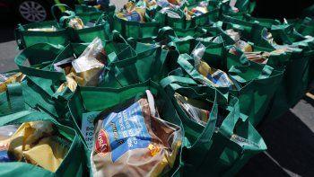 Bolsas con alimentos frescos para ser entregadas en un evento patrocinado por el grupo Greater Chicago Food Depository en el barrio Auburn Gresham de Chicago. (AP Foto/Charles Rex Arbogast)