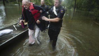 Fred Stewart (izquierda) recibe ayuda del agente de la policía de Splendora Mike Jones tras ser rescatado de su vecindario, anegado por las lluvias de la tormenta tropical Imelda, el 19 de septiembre de 2019, en Splendora, Texas.