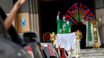 Feligreses asisten a una misa dominical en autocine montada por el padre Jonathan González para eludir las normas que impiden las concentraciones en los templos religiosos, en un estacionamiento en Caracas.