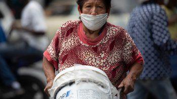 Una mujer, con mascarilla para protegerse del coronavirus, empuja un carrito con recipientes llenos de agua, en Caracas, Venezuela, el 20 de junio de 2020. Se estima que el 86% de los venezolanos reportó problemas con el suministro de agua, incluyendo un 11% que no tiene, según una encuesta realizada por la ONG Observatorio Venezolano de Servicios Públicos entre 4.500 residentes en abril
