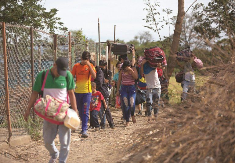 Fotografía del 31 de agosto de 2018 de un grupo de venezolanos que cruzan ilegalmente a Colombia por un camino conocido como trocha
