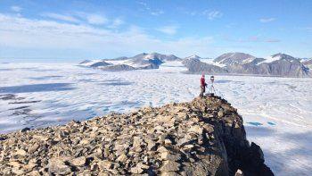 Esta fotografía de julio de 2015, tomada por el profesor de glaciología de la Universidad de Ottawa, Luke Copland, muestra a la analista de hielos Adrienne White, del Servicio Canadiense de Hielos, tomando fotografías de grietas en la plataforma de hielo Milne, que se ha roto a finales de julio de 2020.