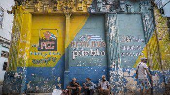 En esta fotografía de archivo del 23 de diciembre de 2020, personas con máscaras mal ajustadas utilizadas contra la propagación del coronavirus se sientan en una acera junto a un muro con consignas políticas en La Habana, Cuba.