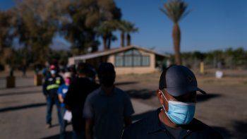 Jornaleros agrícolas hispanos hacen fila para recibir la vacuna de Pfizer-BioNTech contra el COVID-19 el jueves 21 de enero de 2021, en Mecca, California.