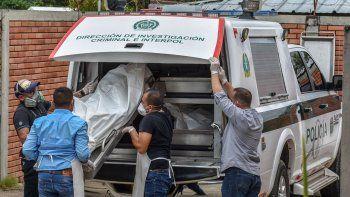 Miembros de la fuerza policial descargan los cuerpos de las víctimas de una masacre presuntamente a manos de grupos armados en el municipio colombiano de Arauca, cerca de la frontera con Venezuela. Morgue de Arauca, 22 de agosto de 2020.