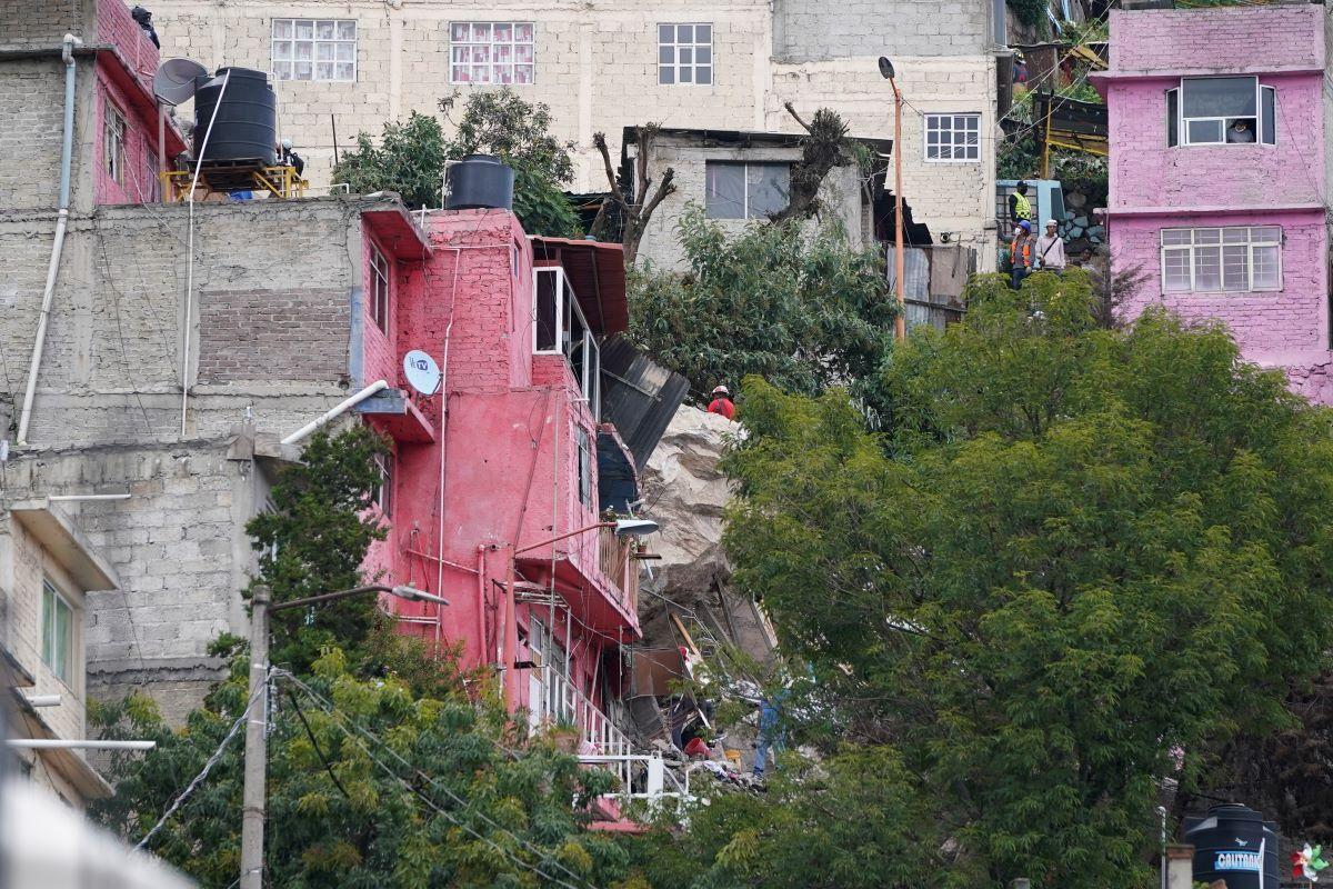 Bomberos escalan una pila de rocas de tres pisos de altura en Tlalnepantla, en las afueras de la Ciudad de México, el viernes 10 de septiembre de 2021, luego de un deslave.